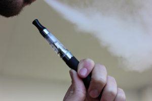 Holding Vape Pen and exhaling vapor